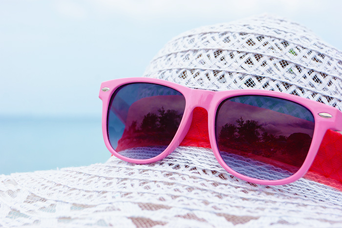 Pink sunglasses on a white hat