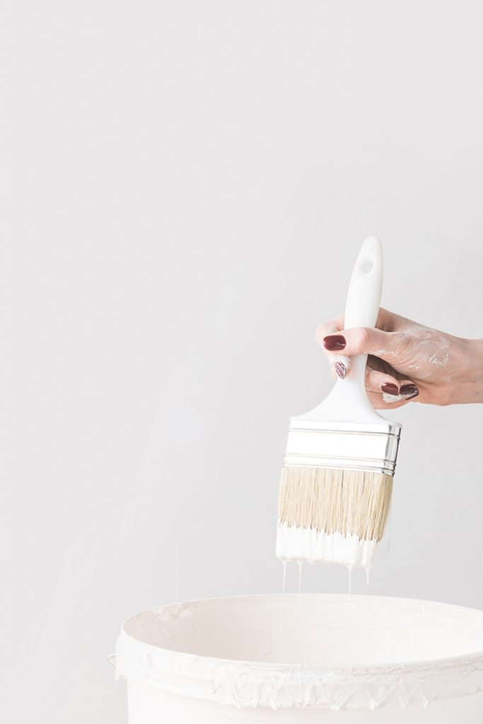 Woman holding brush with white paint