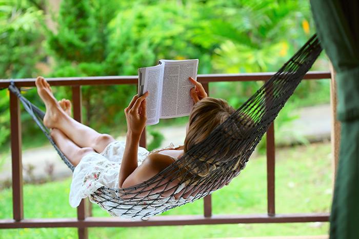 Woman reading near green area