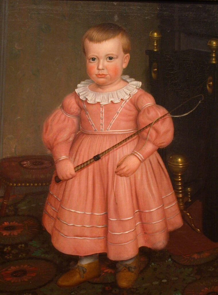 Young boy with a whip wearing a pink dress