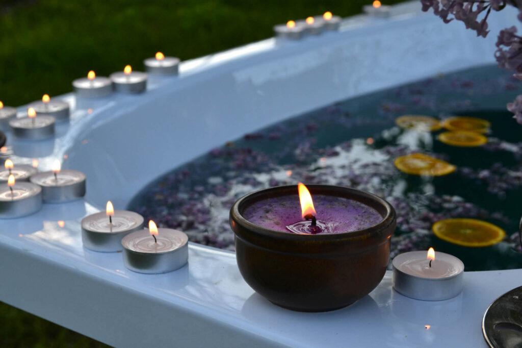 Purple candle on bathtub edge