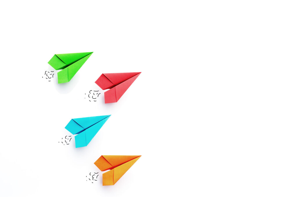 Green, red, blue, orange paper airplanes on white background