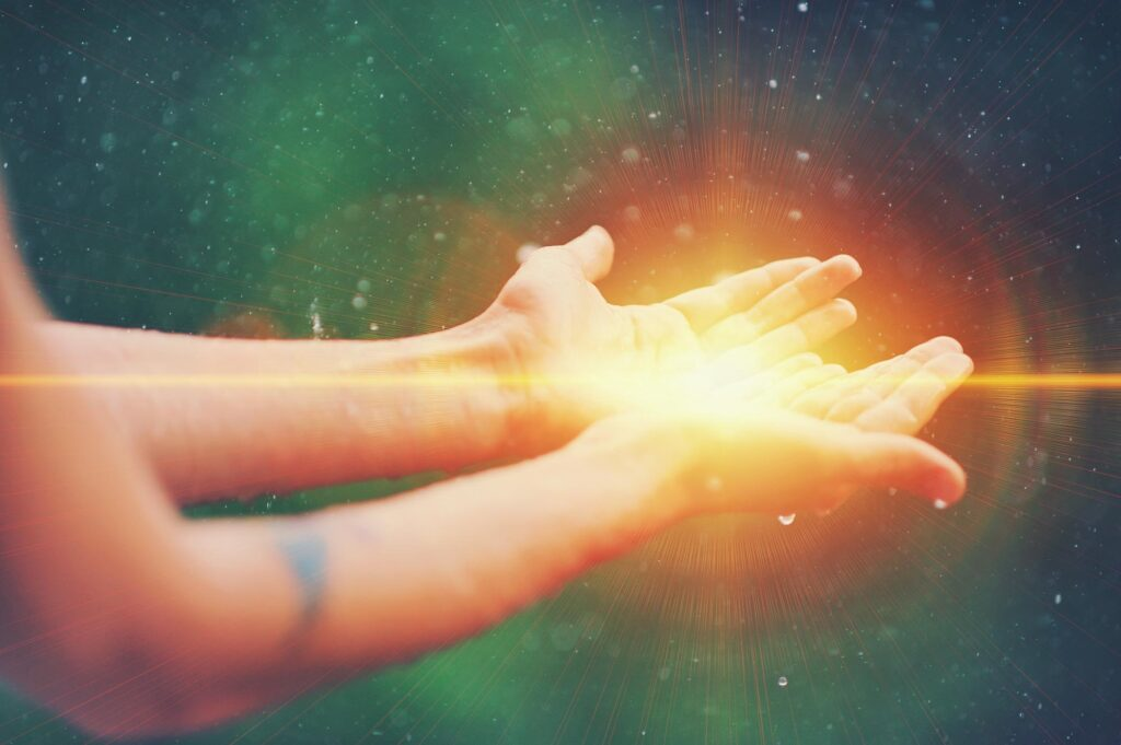 Hands praying holding light with healing colors