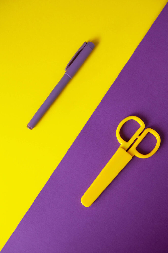 Yellow and purple pen and scissors