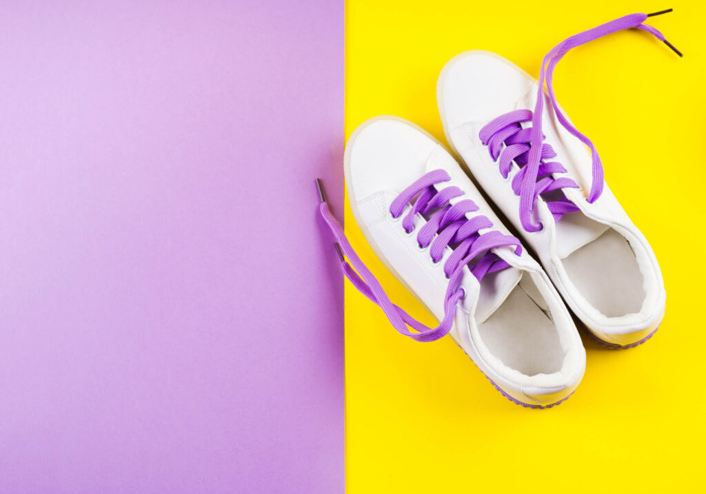 Purple and yellow background with white sneakers