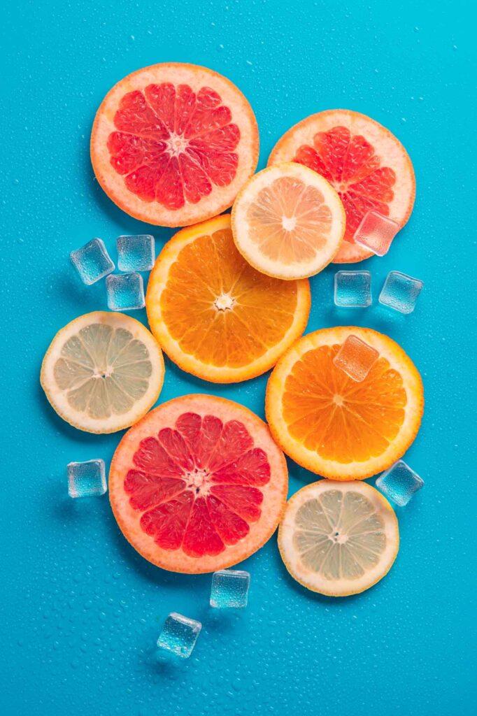 Orange and red grapefruit slices on blue background