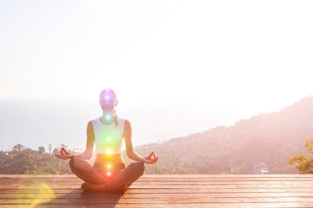 Woman meditating while shining chakra colors for healing