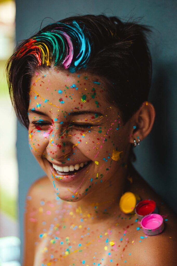 Woman smiling with colorful paint on her face