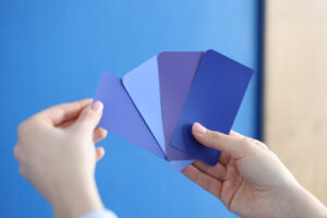 Hands holding different shade, tint, and tone of blue papers